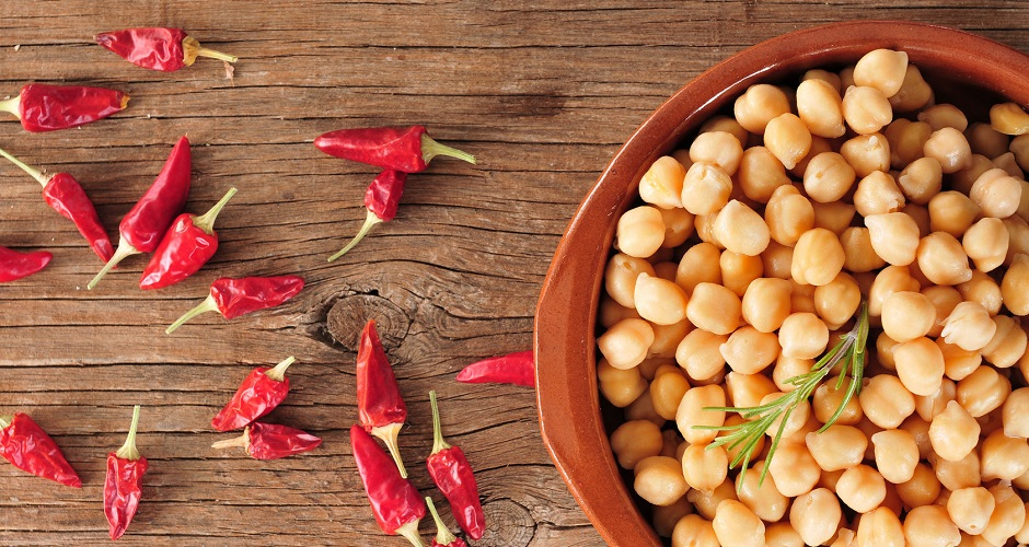 50221784 - high-angle shot of an earthenware bowl with cooked chickpeas and some red chili peppers on a rustic wooden table