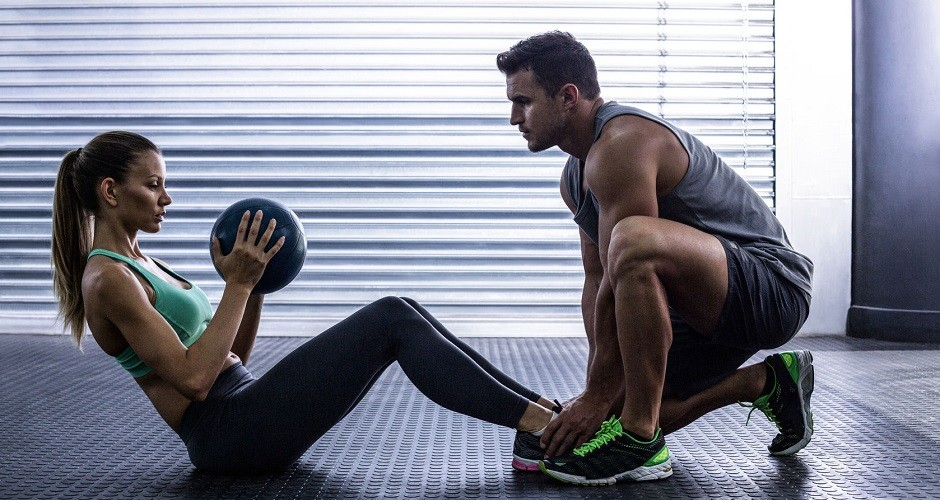 42329550 - side view of a muscular couple doing abdominal ball exercise