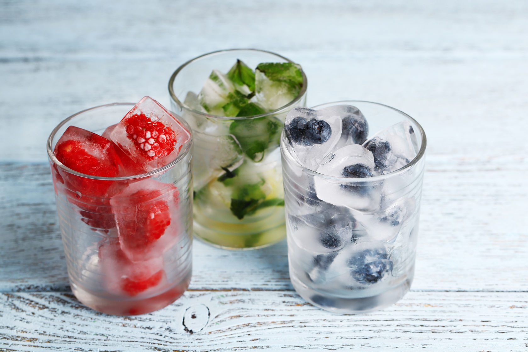 30502713 - ice cubes with mint leaves, raspberry and blueberry in glasses, on color wooden background