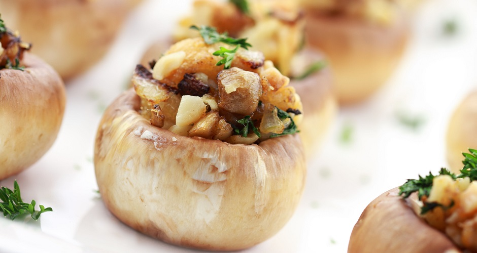 7905667 - stuffed mushrooms filled with bread crumbs, cheese, mushroom stems, fresh parsley,onions and macadamia nuts. extreme shallow dof with selective focus on center mushroom.