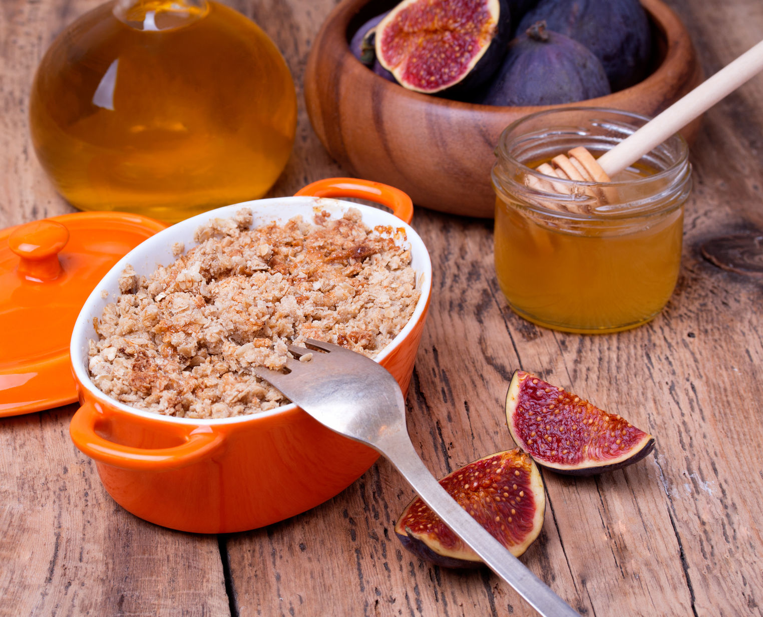 32337930 - apple and figs crumble in orange ceramic dish with honey on wooden background