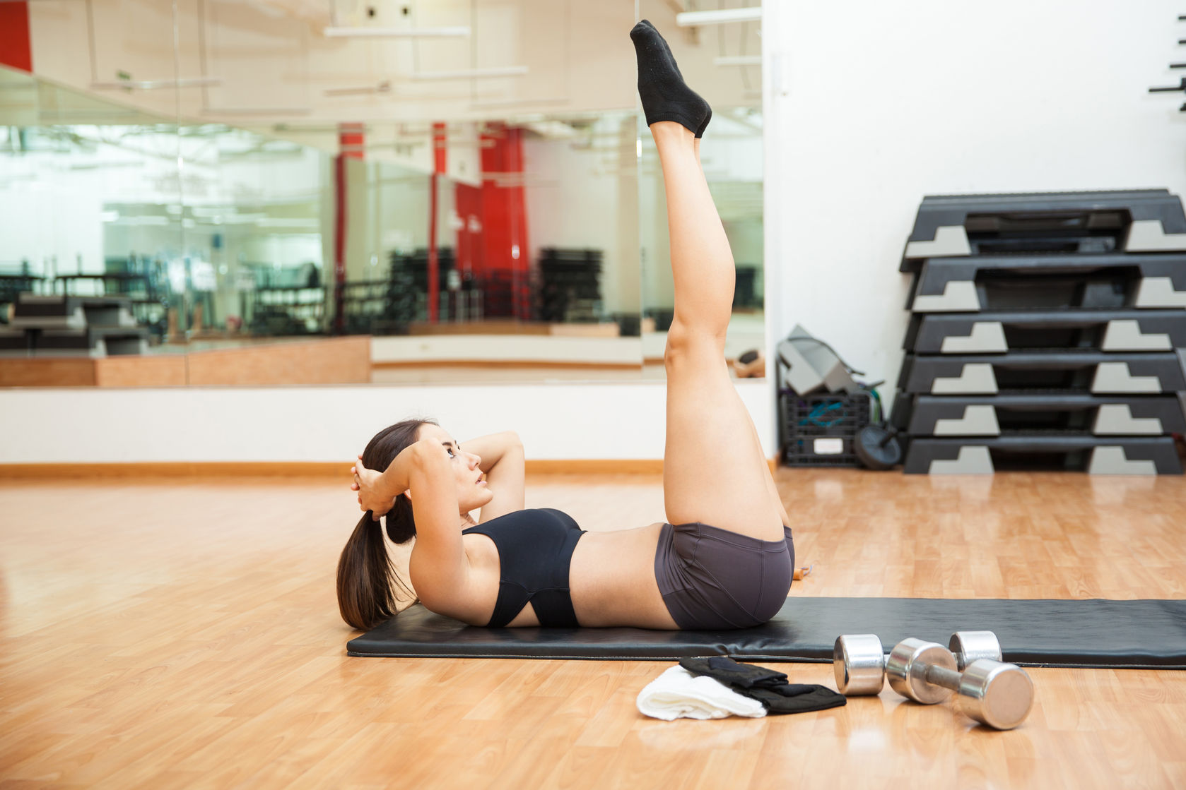 54131949 - profile view of a beautiful young hispanic woman raising her legs and doing crunches at a gym