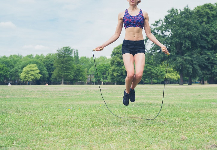 42882990 - a fit and athletic young woman is skipping with a jump rope in the park on a summer day