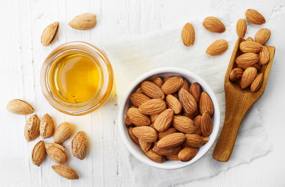 55245854 - almond oil and bowl of almonds on white wooden background. top view