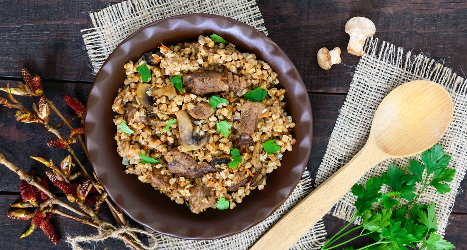 77481918 - buckwheat porridge with pieces of meat and mushrooms on a dark wooden background. top view.