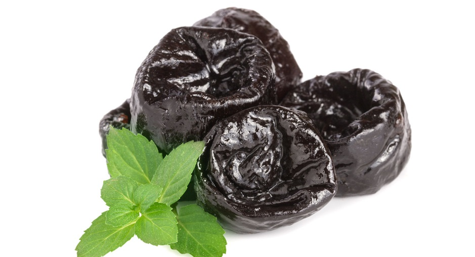 83893853 - heap of dried plums or prunes with a mint leaf isolated on white background